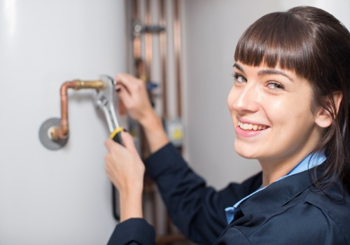 A technician making adjustments to piping, as part of IL Boiler Services