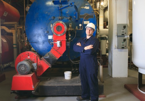A technician standing in front of a new boiler during Boiler Replacement in IL