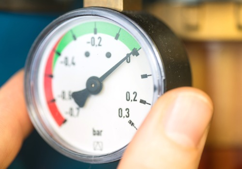 A technician checking a heater control gauge during Industrial Boiler Services in IL