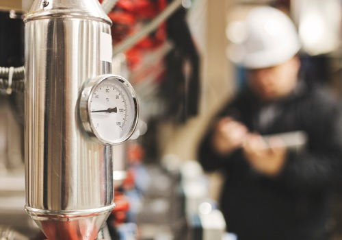 A closeup of a gauge as a technician performs a Boiler Inspection in IL in the background