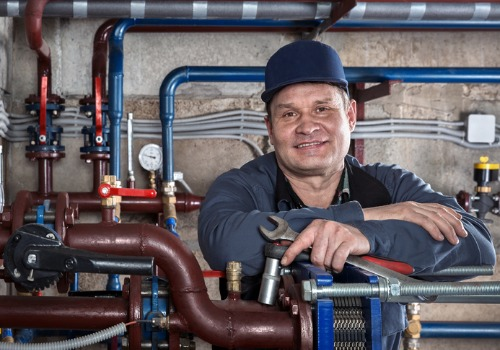 One of Our Commercial Heating Contractors Posing by Some Piping
